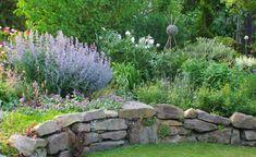 Es braucht nicht unbedingt einen Hanggarten, um das urige Flair einer Trockenmauer genießen zu können. Auch ein Steingarten, ein Hochbeet oder ein tiefergelegter Sitzplatz lassen sich gut mit einem niedrigen Naturstein-Bauwerk einfassen.