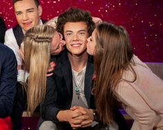 Fans kiss the wax figure of One Direction's Harry Styles at Madame Tussauds in London.