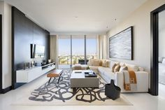 Ultra-modern living room featuring lengthy white pillow backed sectional wrapped around large grey minimalist ottoman is fully sunlit via floor to ceiling glass in distance. Slick dark wood wall on left holds white shelving and media mount.