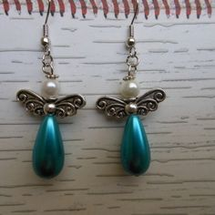 #jewelry #earrings #ccsmallcreations $10  Stainless steel hook earrings with large blue coated glass pearl drop bead, stainless steel wings and a white coated glass round pearl head ...