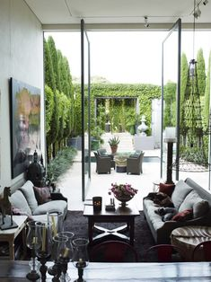 floor to ceiling pivoting glass doors open to walled courtyard . Prue Ruscoe
