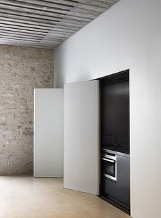 Black kitchen hidden behind minimalist white sliding doors. Ana Noguera. Girona.