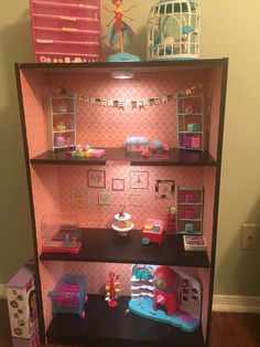 Custom Shopkins storage  I used wall paper for the back drop, target rooms bookshelf and balsam wood for shelves painted with chalk paint and sealed with clear coat. Hot glue the shelf pieces together once cut. Battery operated LED lights per shelf