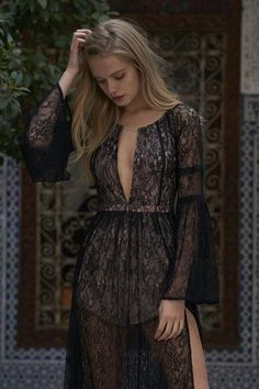 Sheer lace maxi dress with short lining and high slit. Front keyhole neckline and open back with tie closure.