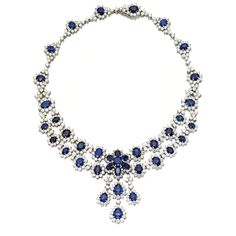 Sapphire and diamond necklace The front designed as swags of floral clusters supporting a triple fringe surmounted by a single larger cluster, the whole set with 39 oval and pear-shaped sapphires weighing approximately 40.00 carats and 489 round diamonds weighing approximately 54.50 carats, mounted in white gold.