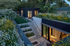 This modern house is sunken down 6 feet from the yard, and a terrace garden leads down to an entry courtyard with a firepit. #Courtyard #Landscaping #GardenDesign #Firepit