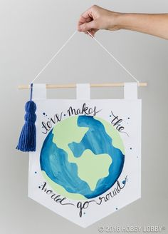 Adventure awaits! Get started on your summer wanderlust with a #DIY globe banner made with canvas and dowel rod. Use watered down acrylics to give it that watercolor feel, and a brush tip sharpie marker to draw out your quote. Add a tassel to make it pop!