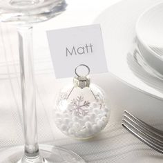 Six Silver Snowflake Bauble Place Name Holders. Add a touch of sparkle to your table with these silver snowflake bauble place name holders! Embellished with silver snowflakes and a sprinkling of snow within - these lovely decorations are a stylish way to direct your guests to their seats. Each bauble holds a square of card with plenty of space to write in your guests' names. Ideal for christmas, winter weddings, New Year's Eve and silver or snow themed parties. #newyearseve #tabledecorations
