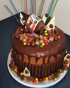 Nutella Boy's birthday cake. Six layers of chocolate cake sandwiched with layers of ganache and Nutella flavored smbc. Iced in Nutella smbc, a ganache drip, chocolate finger biscuits, malteasers, chocolate shards, and chopped up chocolate bars