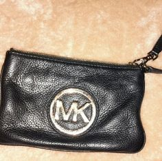Michael Kors black Fulton  leather wristlet/clutch Michael Kors black Fulton leather wristlet/clutch. Great shape, soft leather outside with signature lining inside. Card slots insie lined in leather. MK medallion on front in gold(some scuffs on it). I'm selling because I have too many black wristlets. Michael Kors Bags Clutches & Wristlets