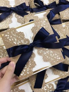 Laser cut wedding invitation with the warm tones of rose gold in metallics and a navy blue ribbon. Discover it on elegantweddinginvites.com!