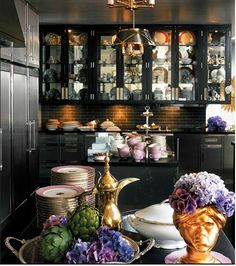 This picture really captivates me, I don't know what I like better the black cabinetry or the pink dishes :)