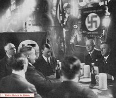 """Hitler and the """"Old Fighters"""" meet in the Hofbräuhaus on 24 February 1929 to mark the anniversary of the famous speech. Left-right: Gregor Strasser, Karl Fiehler (back to camera), Christian Weber, Hitler, Julius Schaub (back to camera), Franz Schwarz, Max Amann. Standing in the background, holding the Blutfahne, is Jakob Grimminger."""