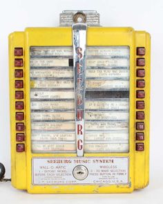 """Lot 17 in the 3.17.15 online & live auction! A vintage 1950s coin operated wall / tabletop jukebox made by J.P. Seeburg Corp., Chicago, IL, USA. The Seeburg Music System """"Wall-O-Matic"""" model requires a nickel deposit before each song selection. The metal box is painted yellow with a row of 10 push-buttons and song title windows on each side. #Music #Decor #1950 #POGAuctions"""