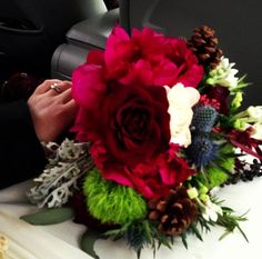 Black bacarra roses, deep red peonies, bright green dianthus, blue thistle, pinecones, white bouvardia, and deep purple juniper berries, are just some of the unique flowers in this gorgeous winter bouquet.  Bridal bouquet Wedding bouquet Red wedding bouquet Christmas Wedding