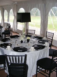 Black lampshade centerpiece with white dendrobium orchids. Black julep cups with lilies and white roses. Black charger plates and napkins. Black chiavari chair