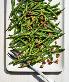 Green Beans With Miso, Mustard, and Walnuts | Green beans scream summer. But how many times have you been dished up slightly over-steamed/over-blanched stalks? Haricots verts, or French green beans, are sold in the produce aisle in little neat packages. If you can't find them, it's okay to use regular green beans. This dish is shockingly simple but full of umami thanks to a couple flavor enhancers. Miso packs punch in the Dijon and rice vinegar dressing. Walnuts aren't just toasted; they're…
