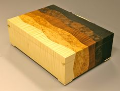 Jewellery box in macassar ebony, pomelle sapele, maple burr, masurbirch and ripple sycamore with a bronze handle. The box is fitted with a maple tray and lined with faux suede