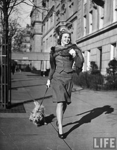 Nina Leen: Actress Joan Caulfield briskly walking her West Highland terrier Witty, down Fifth Avenue past apartment buildings, New York, 1944