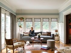 """An Elegant Arts and Crafts """"Forever Home"""" in L. - Here Duprie sits in the sunroom with her dog Polly. A contemporary sofa from Dekor was paired with - Sofa Side Table, Teak Table, Architectural Digest, The Line Apartment, Farmhouse Style Furniture, Amber Interiors, Arts And Crafts Interiors, Contemporary Sofa, White Walls"""