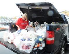 Wendy Panto of Brockton, center, loads six shopping carts into a pickup truck during the grand opening of the Market Basket in Brockton on Tuesday, May 22, 2012. Marc Vasconcellos/The Enterprise