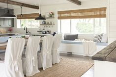 Slipcovered dining chairs, natural roller blinds, blue cushioned window seat!