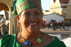 """""""Mama Smile is hét gezicht van 'dushi Boneiru', oftewel: zoet Bonaire. Je vindt de lachende, gezette dame in traditionele kleding overal op het eiland op posters en foto's terug. Maar haar gulle lach herbergt tegenwoordig ook een groene boodschap voor de eilanders en de toeristen: die van de duurzaamheidscampagne Ami ta Konsiente ('Ik ben mij bewust')."""""""
