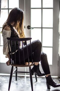 Bohemian rocker style. Over the shoulder top, a cropped vest, and ripped denim with black leather ankle booths.