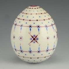 A Russian porcelain Easter egg, circa 1900. The body of the egg decorated with purple and blue geometric motifs against a white ground.