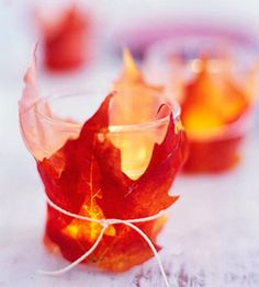 Small candles decorated with autumn leaves gives off a simple orange and red glow, perfect for fall!