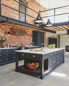 Industrial style shaker kitchen against exposed brick wall with steel beams overhead and industrial lighting. Kitchen by Tom Howley. Farmhouse Kitchen Decor, Industrial Decor Kitchen, Industrial Kitchen Design, Kitchen Remodel, Kitchen Design, Industrial Farmhouse Kitchen, Industrial Kitchen Lighting, Kitchen Trends, Shaker Kitchen