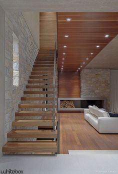 I love these kind of stairs that are open & light & very structural. And the juxtaposition of warm woods with the stone connected by the wood box/ fireplace. A great room overall!