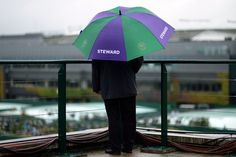 A steward oversees the grounds under an umbrella #Day5 Friday 28th June 2013