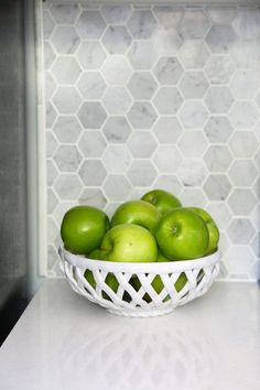 Apples in a bowl, Carrara marble hexagon backsplash. Beautiful white IKEA SEKTION GRIMSLOV kitchen with aqua and green accents, a gorgeous marble hexagon backsplash, and quartz countertops. | http://JustAGirlAndHerBlog.com