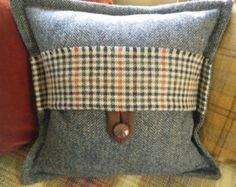 Harris tweed cushion with vintage tweed accent fabrics and button. Makers and tweed authority labels sewn on the inside in accordance with my habit and tradition!  Each tweed in this particular cushion has a different pattern in the weave, which is clearly shown in the close-up of the tab closure. This is often the case with all the cushions, but I think it works especially well in this example...if I do say so myself ; )  * Approx 18 square  * Feather insert included  * Kindly enquire…