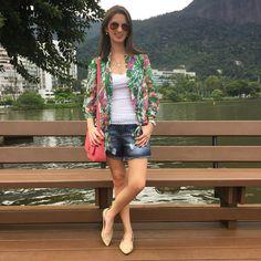 Look com short jeans destroyed, regata branca, camisa floral, bolsa rosa e sapatilha nude.