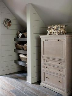 Built-in shelves, tucked into a hidden nook create storage in a space that would have very little functional use otherwise. Efficiently utilizing space for storage allows more public places to appear less cluttered and more put together. The use of wood as the shelves, on the floor and for the chest of drawers gives the area a rustic look.