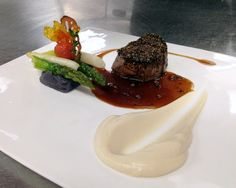 Black pepper crusted filet mignon served with a complimentary black trumpet au jus, cauliflower purée, smashed Peruvian purple potatoes beneath sautéed white and green asparagus and roasted cherry tomato