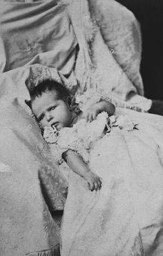 Imperatriz Alexandra Feodorovna enquanto bebê Princesa Alix de Hesse. Ela está deitada e usa vestido longo com mangas curtas. Ela tem um pouco de cabelo escuro. Agosto de 1872.