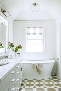Stunning all white bathroom with a freestanding bathtub and gorgeous tan and white geometric print floor tiles. See the rest of this modern and feminine redesign and total gut renovation of a historic San Francisco home on Architectural Digest.