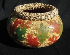I love the carved background of this gourd, the leaves stand out so well - very well done. And the rippled rope rim fits this gourd perfectly. By Cheryl Burns