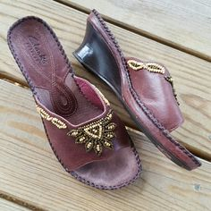 Clarks Beaded Burgundy Leather Sandals Clarks are so comfortable! Worn, but fantastic condition. Some slight wear on the insoles and leather. 2 inch wedge heel. Size 7 & 1/2 Medium. A great dark burgundy color, with tan and dark brownish beading. Clarks Shoes Sandals