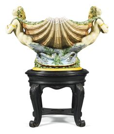 A monumental Minton majolica cistern, circa 1870 modelled as a scallop shell, the handles formed as mermaids with arms crossed holding wreaths, the interior turquoise glazed, raised on an oval shell-moulded base moulded and applied with seaweed, wood stand, impressed factory mark and shape number 1301
