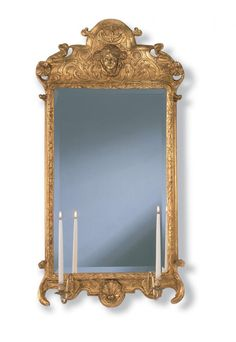 """#7566 WILLIAMSBURG QUEEN ANNE MIRROR 25 x 50"""" The flamboyant Queen Anne gilded looking glass demonstrates late Baroque, English styling from around 1720-40. Found in Wetherburn's Tavern at Colonial Williamsburg, the raised head of a woman, the gessoed repouss decoration and crests with rosettes serve as a testament to the carver's skill. Looking glasses with sconce arms holding candles were used as a way to amplify reflected light in times before electricity. licensee to COLONIAL…"""