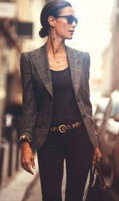 Checked blazer over black top and jeans with brown belt and handbag.