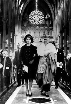 Jacqueline Kennedy being escorted by Richard Cardinal Cushing at the Holy Cross Cathedral in Boston , Massachusetts, on January 19, 1964.