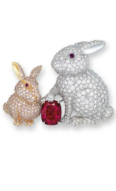 A UNIQUE RUBY, COLOURED DIAMOND AND DIAMOND BROOCH, BY GRAFF Centering upon a cushion-shaped ruby, weighing approximately 6.02 carats, flanked by a pavé-set circular-cut diamond rabbit and a circular-cut pink diamond rabbit, each set with circular-cut ruby eyes, mounted in gold, 5.0 cm