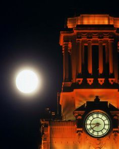 Detail of clock on Main Tower with full moon in background, UT Austin.  It's lit burnt orange on special UT occasions, usually sports championships.