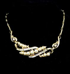 This is a beautiful, gone tone faux pearl and rhinestone necklace. It's unique with a link chain with rhinestone baguettes. It's in great condition. It is signed Coro.