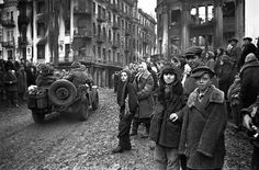 March 1944 Ukrainian civilians in Vinnytsia gather on the city's streets as the Soviet 38th Army, 1st Ukrainian Front, liberate the city from Axis occupation. The city had been under German occupation from 21 July 1941 until 20 March 1944. As the Germans retreated, they started large-scale fires, which can be seen in the building façades. While occupied by the Axis in 1943, the Germans discovered 91 mass graves in three locations throughout Vinnytsia containing the bodies 9,432 people, all…